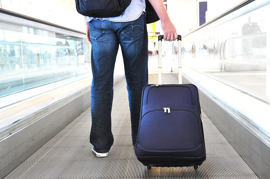 airport traveler with suitcase on walkway, credit bigstock